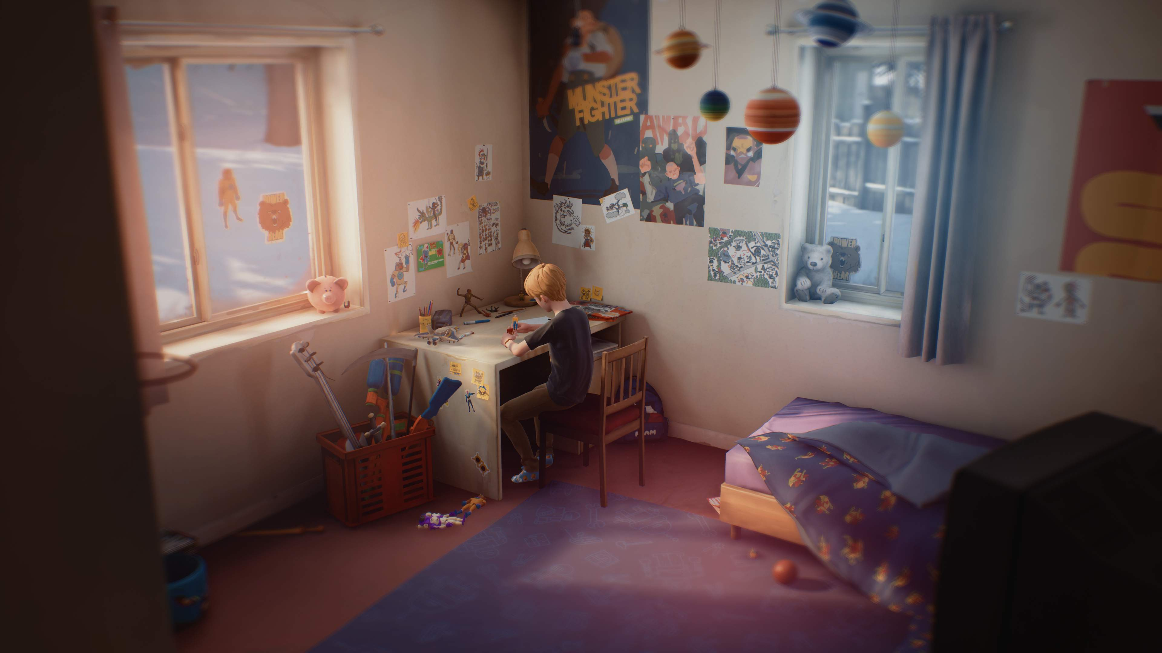 A young boy, Chris, sits at the desk in his bedroom, playing. A display of the planets hangs from the ceiling.
