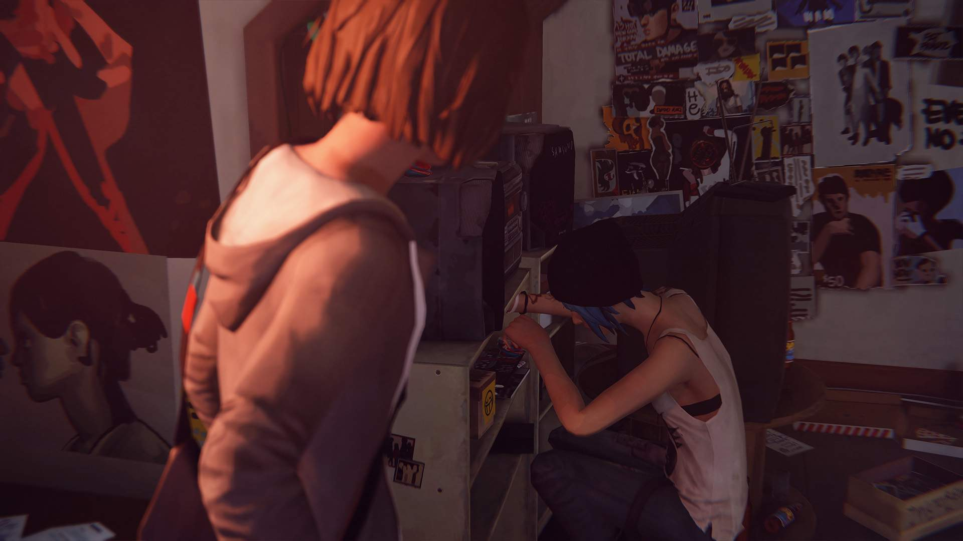 Max looks on as Chloe rummages through her bedroom shelving in search of the perfect CD to play.